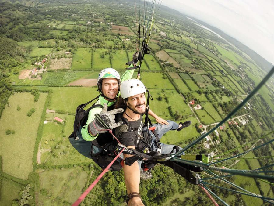 smiling, paragliding, in the air, gopro, fields, landscape, http://wetravelandblog.com